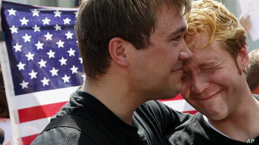 Michael Knaapen, left, and his husband John Becker, right, embrace outside the Supreme Court in Washington, Wednesday, June 26, 2013, after the court cleared the way for same-sex marriage in California by holding that defenders of California's gay ma...