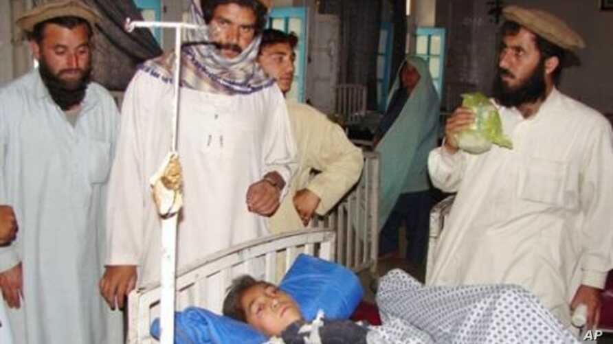 Pakistani tribesmen gather around an injured boy at a hospital in Miranshah, the main town in North Waziristan on following a US drone attack, 22 May 2010