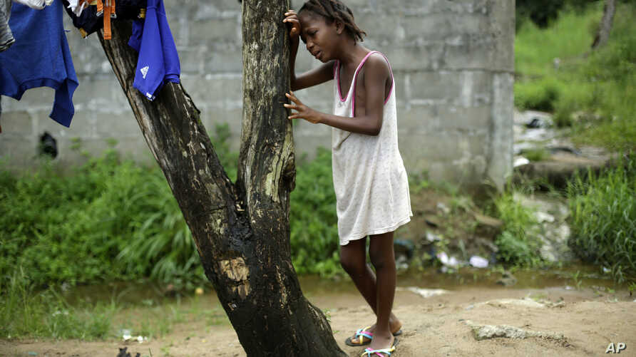 FILE - Mercy Kennedy, 9, cries after learning her mother has died of Ebola, one day after medical workers took her to a nearby hospital in Monrovia, Liberia, Oct. 2014.