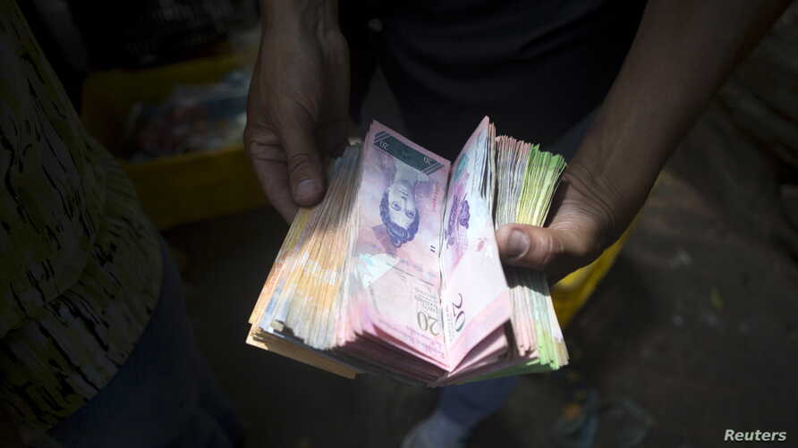 A man displays bolivar notes that he carries to pay for goods at a street market in Caracas, Venezuela, Oct. 1, 2015.