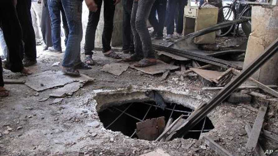 Syrians gather near a crater from a tank shell in a neighborhood of the capital, Damascus, after a raid by Syrian troops killed several rebels and civilians, April 5, 2012.