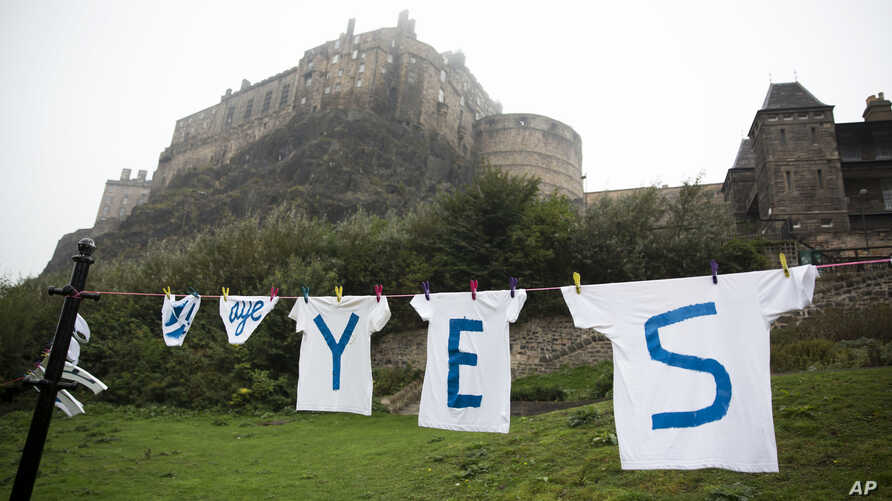A Yes campaign sign for the Scottish independence referendum stands backdropped by Edinburgh Castle, in Edinburgh, Scotland,  Sept. 18, 2014.