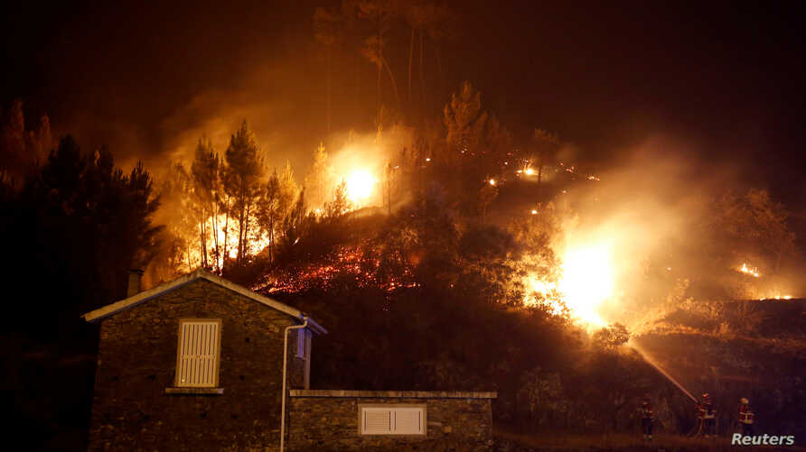 Firefighters work to save a house from a forest fire in Carvalho, near Gois, Portugal, June 19, 2017.