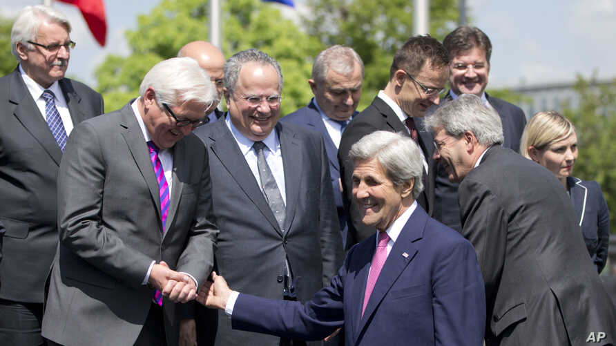 FILE - U.S. Secretary of State John Kerry, center, speaks with German Foreign Minister Frank-Walter Steinmeier, second left, and Greek Foreign Minister Nikos Kotzias, fourth left, during a group photo at NATO headquarters in Brussels.