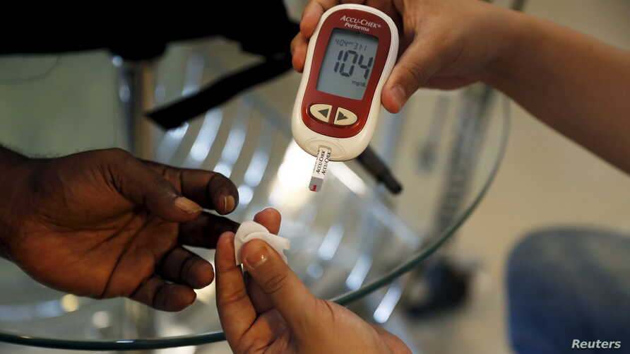FILE - A paramedic checks the blood sugar level of a patient at a diabetes clinic in Jakarta, Indonesia, April 22, 2016.