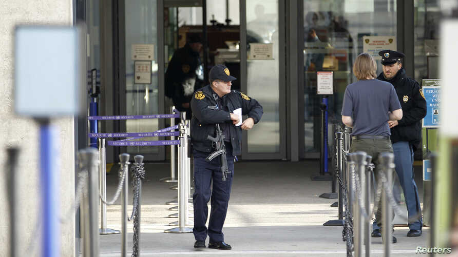 A U.S. security guard stands outside the U.N. European headquarters in Geneva, Switzerland, Dec/ 10, 2015. Geneva officials said Thursday they had raised the level of alert and were looking for suspects by identified by Swiss federal authorities.