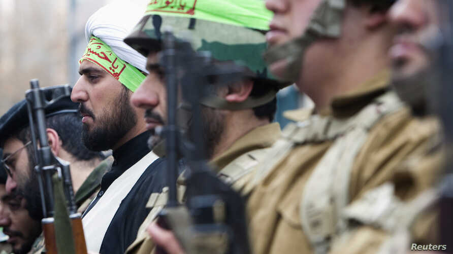 FILE - A cleric, who is member of Iran's Basij militia, attends a military parade to mark Basij week in front of the former U.S. embassy in Tehran, Nov. 25, 2011.