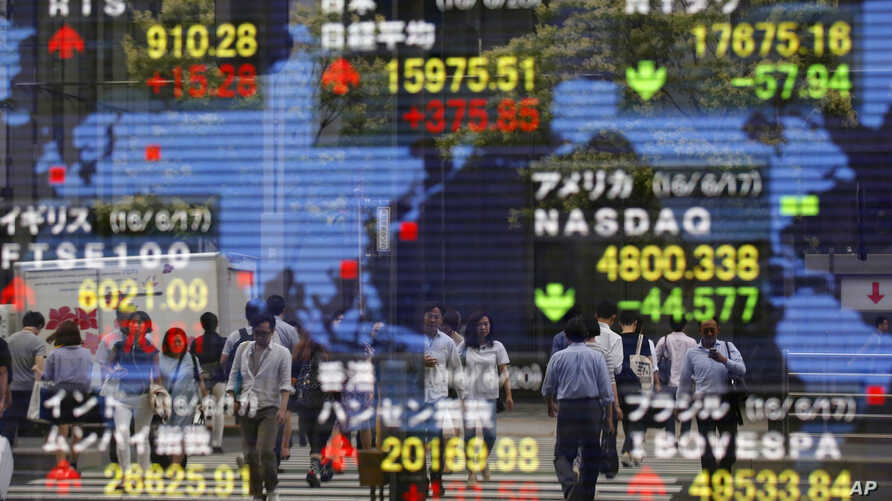 A securities firm's electronic stock indicator reflects pedestrians passing by in Tokyo, June 20, 2016. Global markets jumped Monday as polls suggest British voters on Thursday will choose to remain in the European Union.