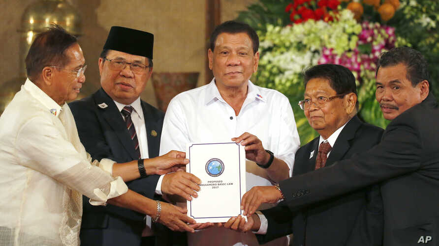 Philippine President Rodrigo Duterte, center, holds the draft of the Bangsamoro Basic Law (BBL) together with, from left, Secretary Jesus Dureza, government Peace Panel chief negotiator, Al-Hajj Murad, chair of Moro Islamic Liberation Front (MILF), G