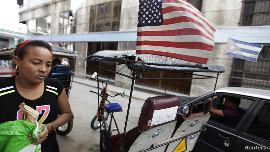 FILE - A woman walks past a bicycle taxi displaying the U.S. and Cuban flags in Havana December 17, 2014.