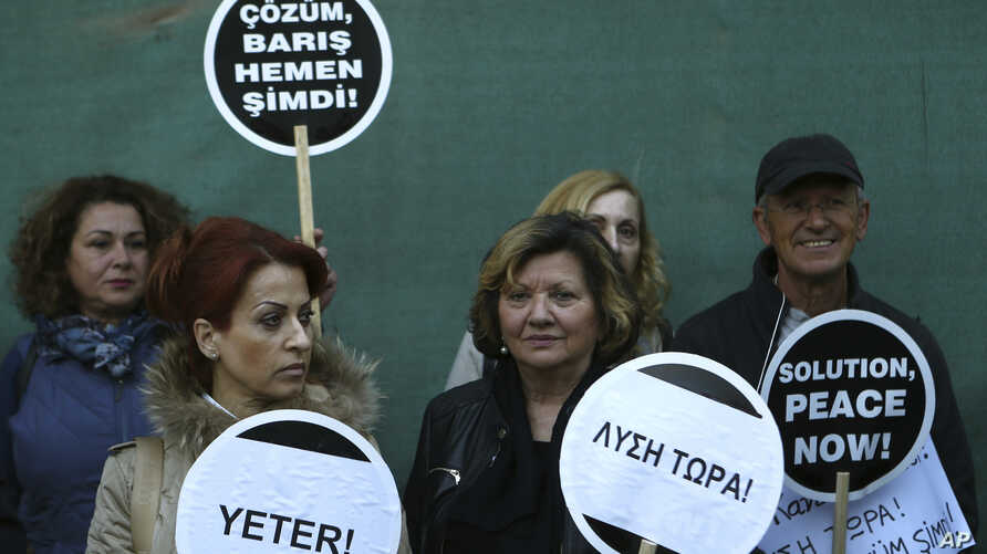 "Greek and Turkish Cypriots holds banners reading in Greek, Turkish and English ""Solution Now"" as they stand in front of the main gate of the Ledras Palace, where the United Nations envoy will host a dinner with ethnically divided Cyprus' rival leader"
