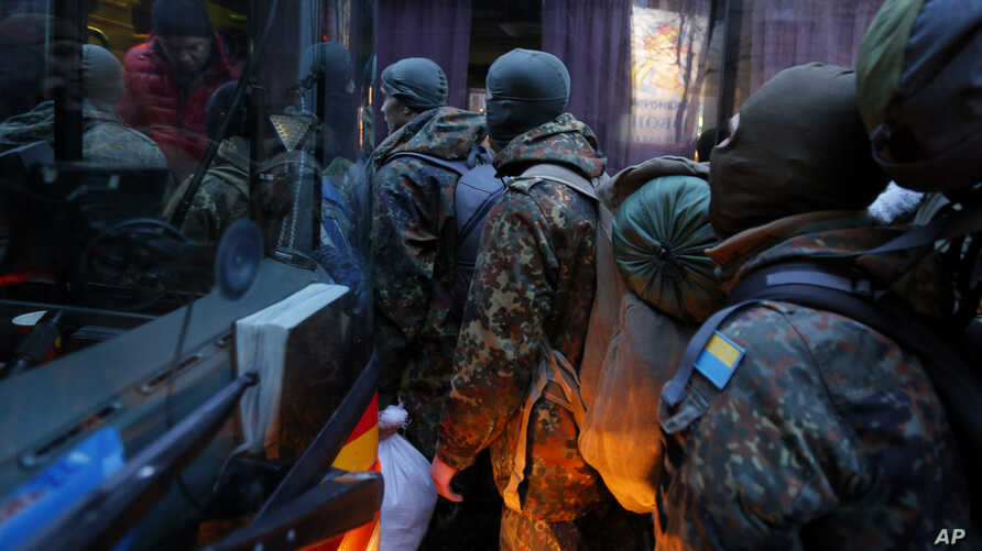Volunteers from the Azov battalion get on a bus bound for the eastern part of Ukraine to join the fighting against pro-Russian separatists in Kiev, Jan. 17, 2015.