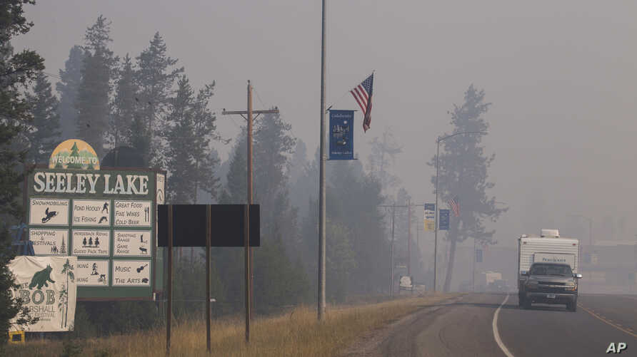In this photo provided by the U.S. Forest Service a pickup pulls a camper through the wildfire smoke in Seeley Lake in Missoula County, Mont., Aug. 10, 2017. Health officials in western Montana are strongly recommending residents of Seeley Lake leave...