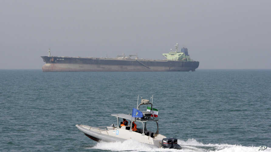 In this July 2, 2012 file photo, an Iranian Revolutionary Guard speedboat moves in the Persian Gulf while an oil tanker is seen in background. (AP Photo/Vahid Salemi, File)