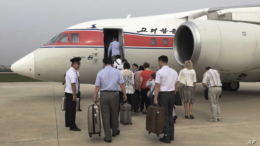 FILE - Passengers board an Air Koryo flight headed for Beijing in Pyongyang, North Korea, June 27, 2016. Air Koryo runs at least one gas station and car wash in Pyongyang, has its own fleet of taxis and operates several retail shops, including a bout