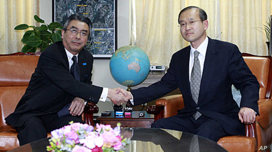 Japanese nuclear envoy Shinsuke Sugiyama, left, shakes hands with his South Korean nuclear envoy Lim Sung-nam before their meeting at Foreign Ministry in Seoul, South Korea, January 12, 2012.