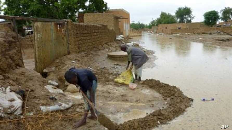 People protect their houses from flood water after torrential rain brought down buildings (file photo - 31 Aug 2010)