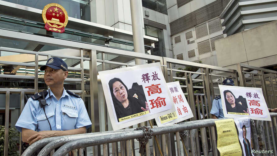 A policeman stands guard next to portraits of Chinese journalist Gao Yu during a demonstration calling for Gao's release from a prison in China, outside the Chinese liaison office in Hong Kong, April 17, 2015.