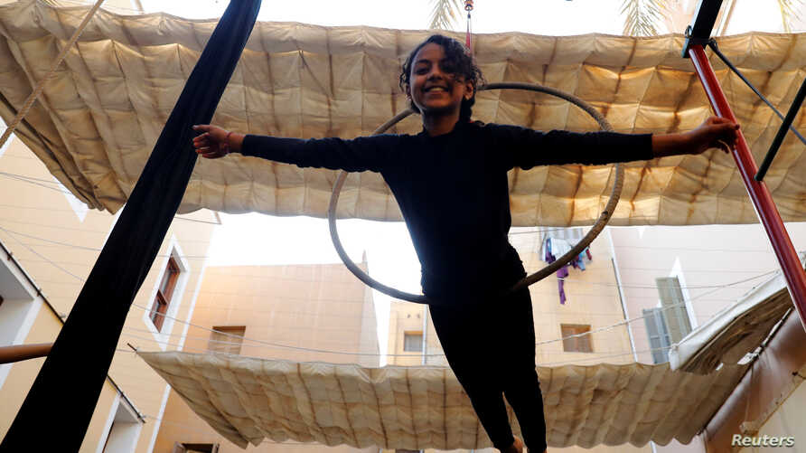 """A girl performs with hanging hoops during a training session at al-Darb al-Ahmar Arts School """"DAAS"""" where children learn circus skills and arts in old Cairo, Egypt, July 17, 2018."""