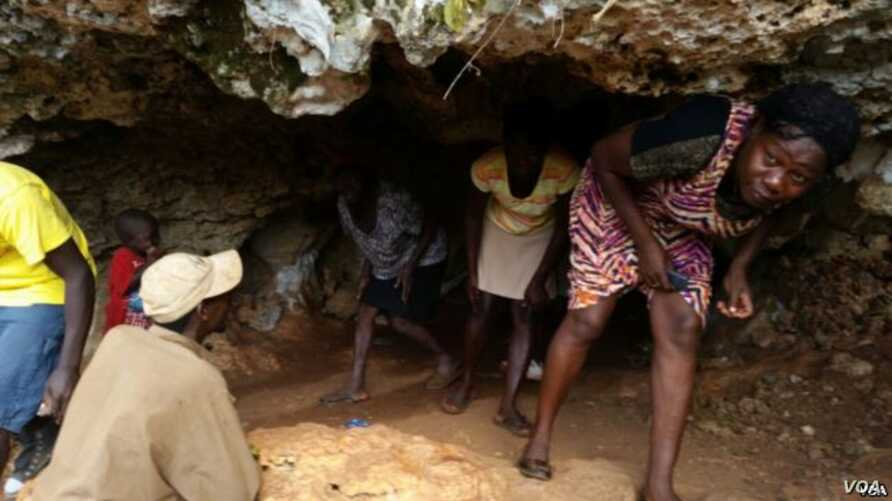 People emerge from a cave near Jeremie, Haiti, where scores continue to seek shelter after their homes were damaged or destroyed by Hurricane Mathew last October. (B. Magloire for VOA)