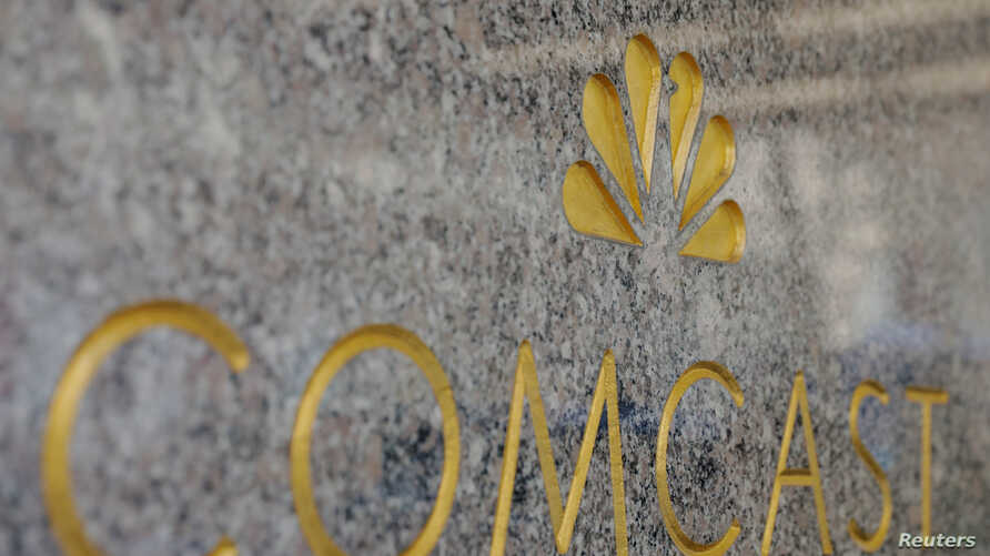 FILE - The NBC and Comcast logos are displayed on 30 Rockefeller Plaza in midtown Manhattan in New York.