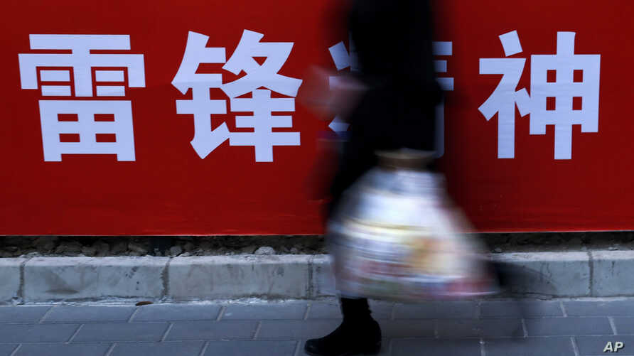 """A woman carries her groceries past a Chinese propaganda board depicting """"Lei Feng Spirit"""" on a pavement in Beijing,  March 5, 2019."""