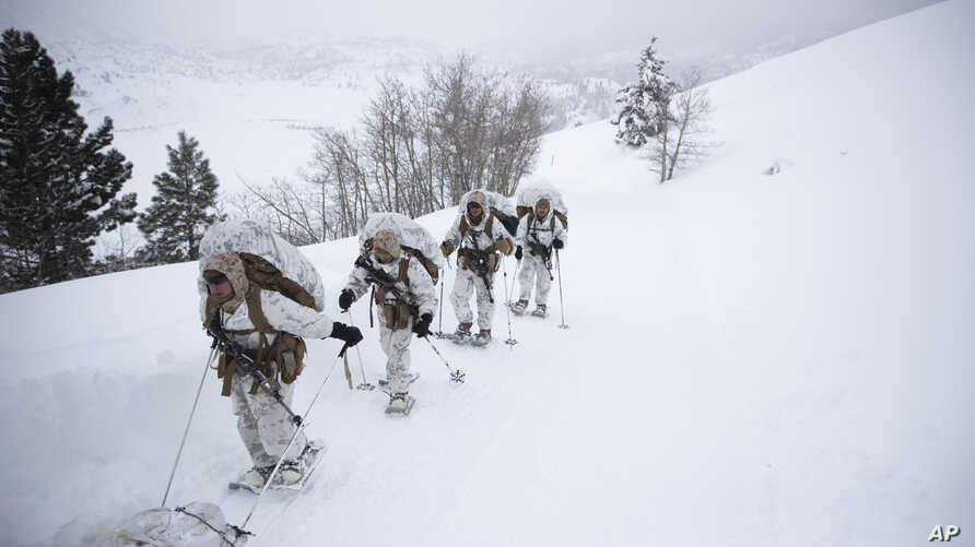 A group of U.S. Marines walk along a snow-covered trail during their advanced cold-weather training at the Marine Corps Mountain Warfare Training Center, Feb. 10, 2019, in Bridgeport, Calif.