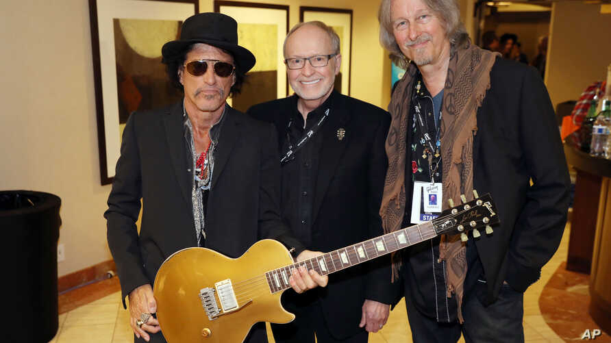 Image distributed by Gibson Brands shows Musician Joe Perry (L), Dave Berryman, President of Gibson Guitar (C), and Peter Leinheiser, Senior Director of GIbson Entertainment Relations, posing together after Perry was presented a Gibson Custom Made 2