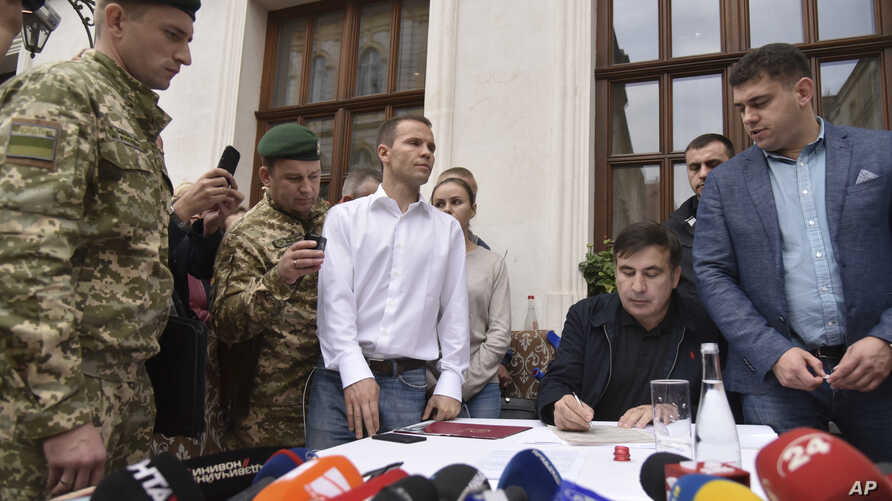 Former Georgian president and ex-governor of Ukraine's Odessa region Mikhail Saakashvili, second right, signs a protocol on border crossing at a hotel in Lviv, Ukraine, Sept. 12, 2017.