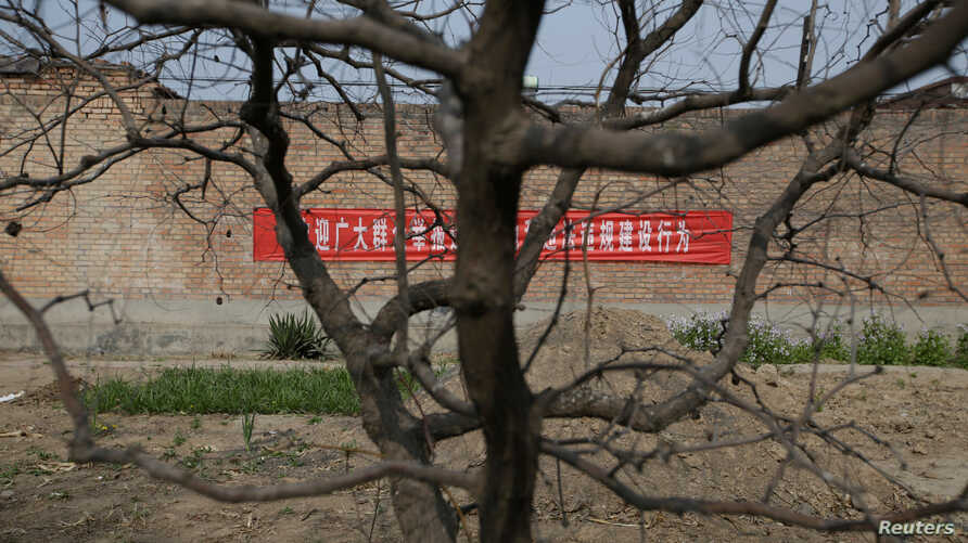 A banner warning against illegal land occupancy is placed on a wall in Santai, one part of the new special economic zone Xiongan New Area, China, April 6, 2017.