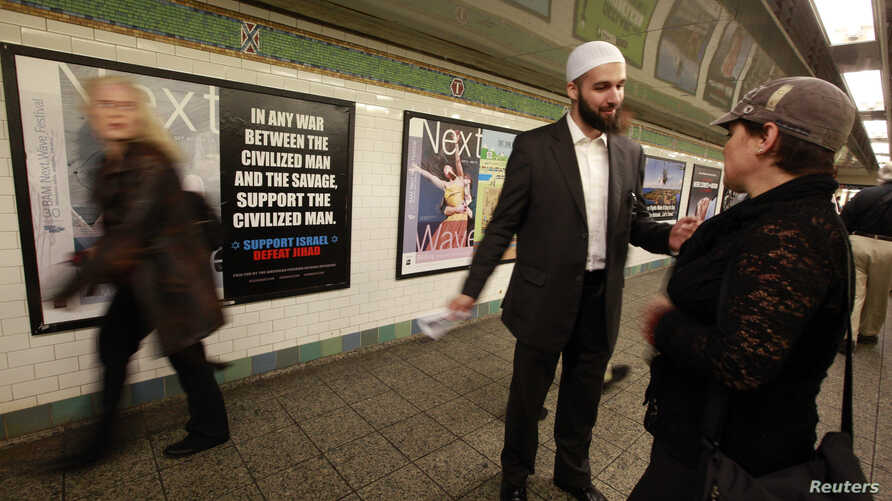FILE - Cyrus McGoldrick, a member of the Council on American-Islamic Relations, talks to a woman in the Times Square subway station in New York.
