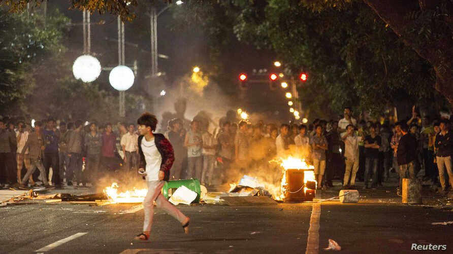 Demonstrators set fire to trash cans as they protest against a chemical plant project, on a street in Maoming, Guangdong province, China, early April 1, 2014.