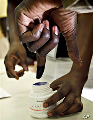 A prospective Sudanese voter dips his finger in ink at a voter registration facility in Glendale, Arizona, 26 Nov. 2010