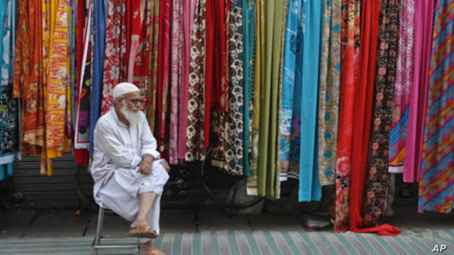 A man selling fabric waits for customers at a roadside stall in Lahore, Pakistan, September 25, 2011.