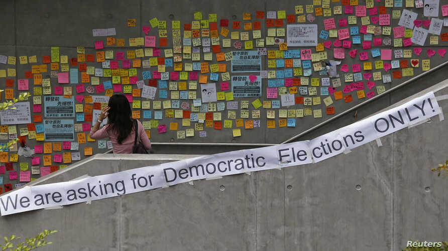 A woman looks at notes left by pro-democracy protesters on a footbridge in Hong Kong, Oct. 2, 2014.