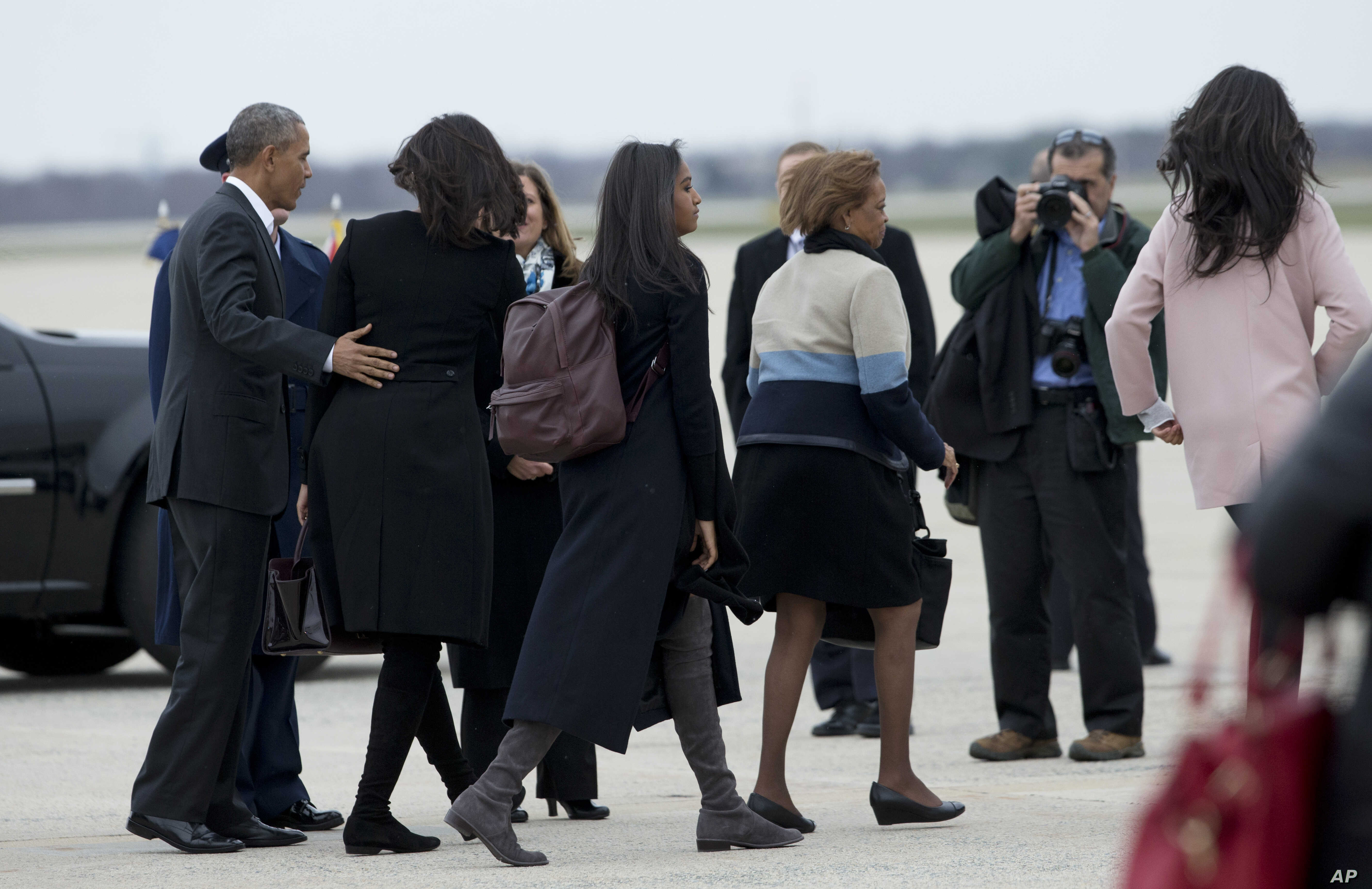 The first family, from left, President Barack Obama, Michelle Obama, their daughters Sasha and Malia, and mother-in-law Marian Robinson, fourth from left, walk to board the Air Force One for a trip Havana, Cuba, March 20, 2016.