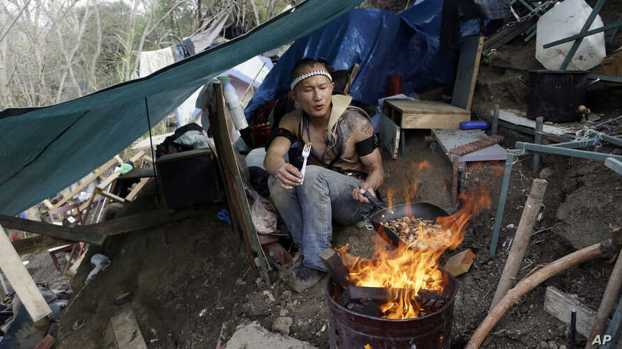 FILE - A man who goes by the name of D cooks lunch from a makeshift tent where he lives in the Jungle, a homeless encampment in San Jose, California, March 4, 2014.