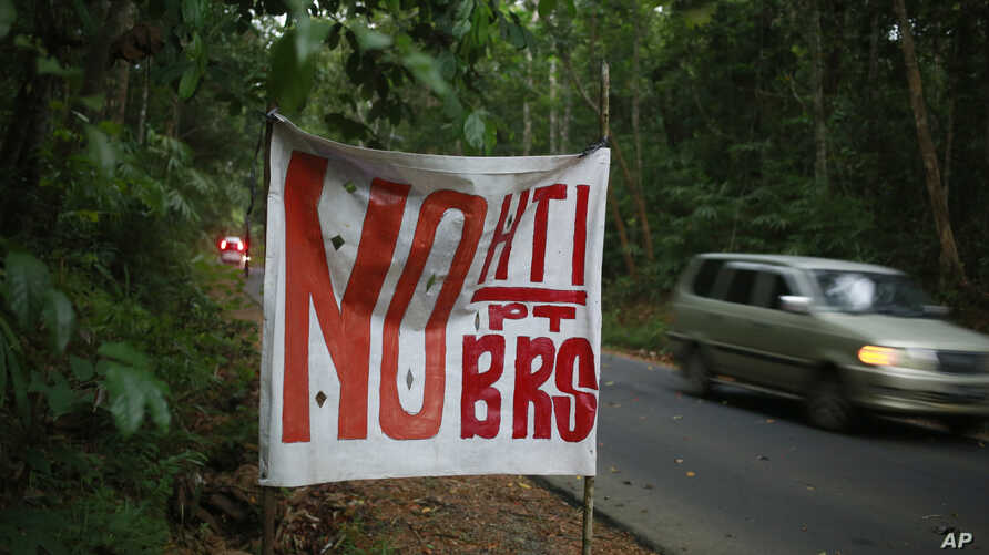 "In this June 13, 2017, photo, a sign that reads ""no to industrial forestry plantations and BRS,"" a reference to Bangun Rimba Sejahtera, the company that's a front for Asia Pulp & Paper's expansion in the area, is put up on a roadside in West Bangka,"