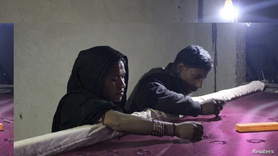 Mohammud Sanu and his wife work on fine needlework by the light of a solar lamp in Pipargaon Nevada village, in the Indian state of Uttar Pradesh, Jan. 9, 2018.