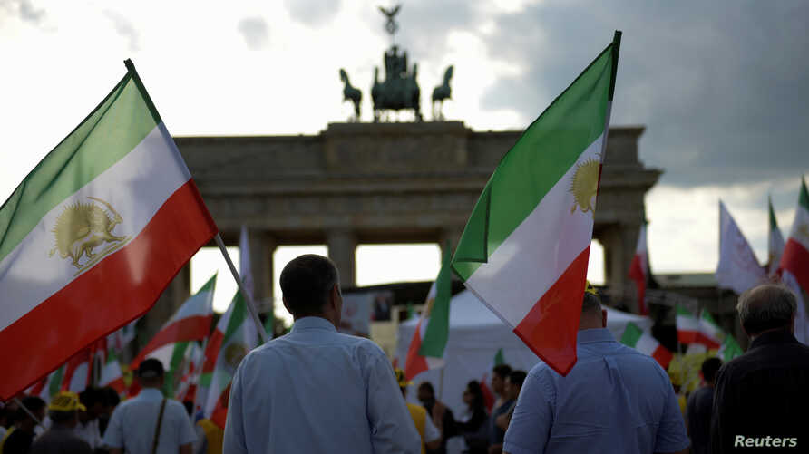 Activists hold flags during a demonstration against executions in Iran in Berlin, Germany, Sept. 3, 2016.