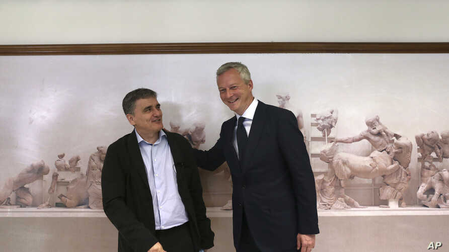 French Minister of the Economy and Finance Bruno Le Maire , right, meets with his Greek Finance Minister Euclid Tsakalotos in Athens, June 12, 2017. Their meetings in Athens are aimed at ending a months-long delay in a rescue funding agreement betwee