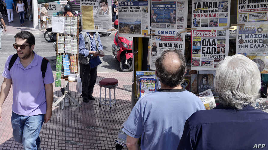 People read newspaper's headlines in central Athens  on June 15, 2015.