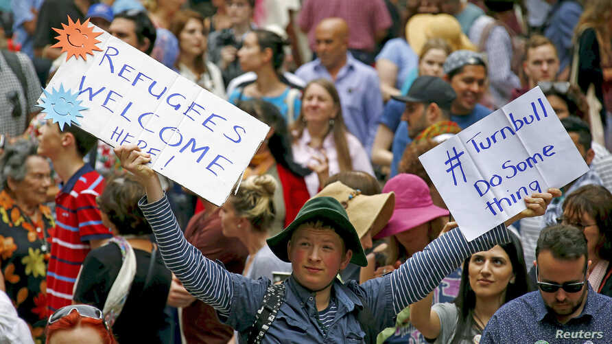 Demonstrators hold placards during a rally in support of refugees that was part of a national campaign in central Sydney, Australia, Oct. 11, 2015.