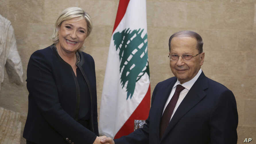 In this photo released by Lebanon's official government photographer Dalati Nohra, French far-right leader and presidential candidate Marine Le Pen, left, shakes hands with Lebanese President Michel Aoun, at the presidential palace, in Baabda, east B
