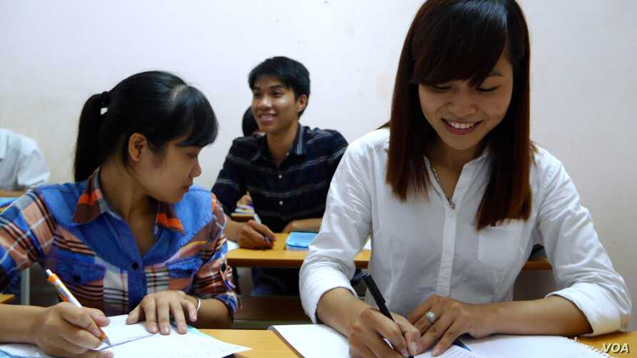 Student Pham Thi Trang (right) studies Japanese at a free language school set up by a street vendor, Hanoi, Vietnam, Aug. 7, 2014. (Marianne Brown/VOA)