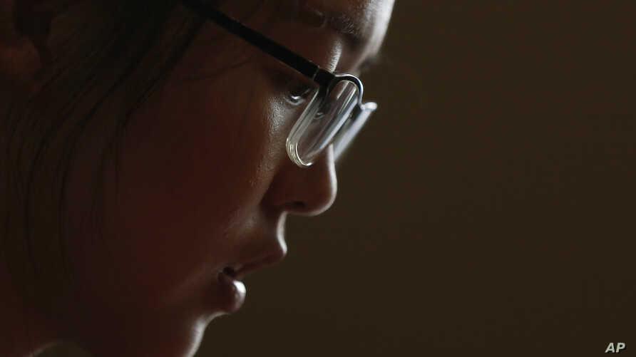 In this July 3, 2018, photo, Ren Liping pauses during an interview after filing her petition to have her rape allegation case reexamined in Beijing.