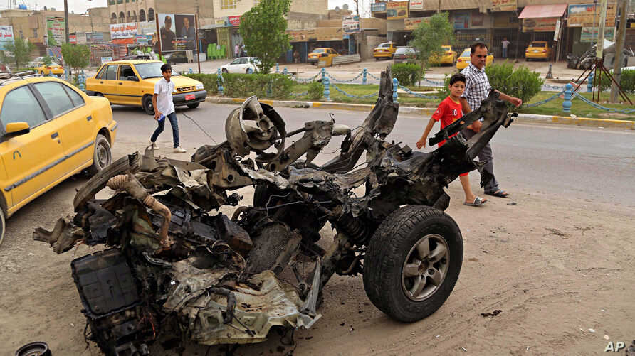 Civilians pass a destroyed car in the a car bomb explosion in southwestern Baghdad, Iraq, May 20, 2017.