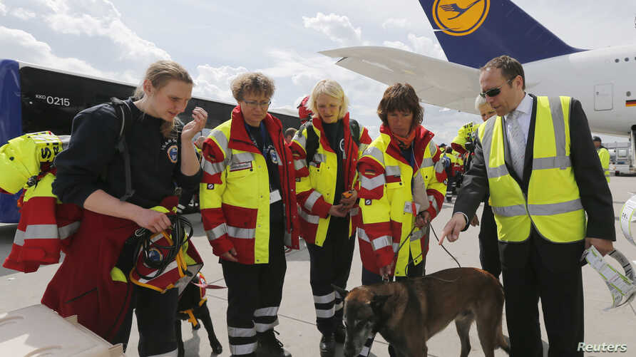 Members of Germany's NGO organization International Search and Rescue (ISAR- Germany) prepare sniffer dog Apache to board their flight to Nepal from Frankfurt airport, April 26, 2015.