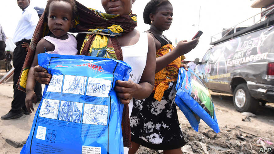 A woman carrying a baby holds a treated mosquito net during a malaria prevention action at Ajah in Eti Osa East district of Lagos, Nigeria, April 21, 2016.