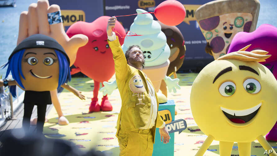 """FILE - Actor T. J. Miller poses with characters for the film """"The Emoji Movie,"""" at the 70th international film festival, Cannes, May 16, 2017."""
